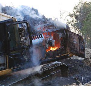 Tela-alustaisien kaivuukoneen moottori tulessa